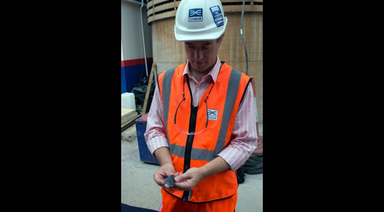 94382_Crossrail Lead Archaeologist Jay Carver holding mesolithic flint found at North Woolwich site